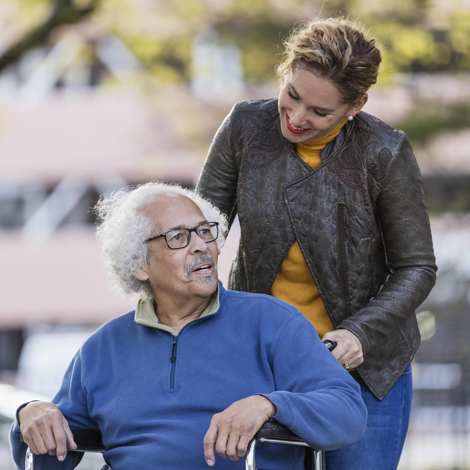 A senior Hispanic man in his 80s sitting in a wheelchair, talking to his adult daughter, who is in her 30s, pushing the wheelchair from behind. They are walking in a city park in fall, building out of focus in the background.