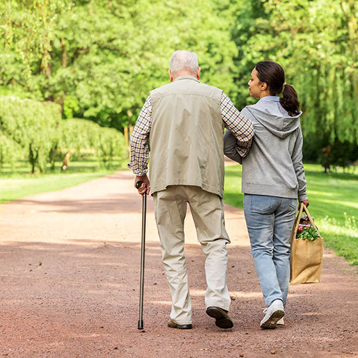 older man with cane walking with caregiver