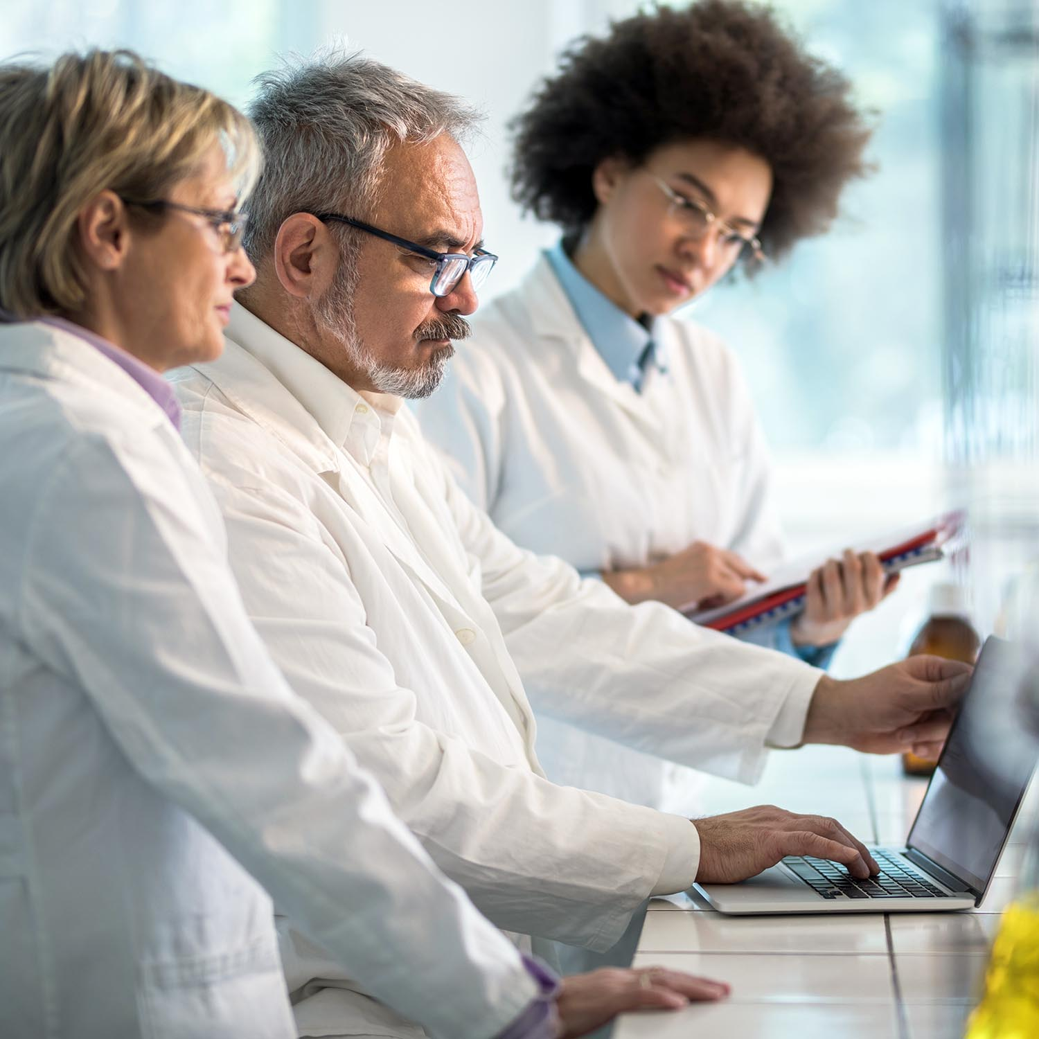 Three biochemists working on laptop in a laboratory. Focus is on mature man typing on laptop.