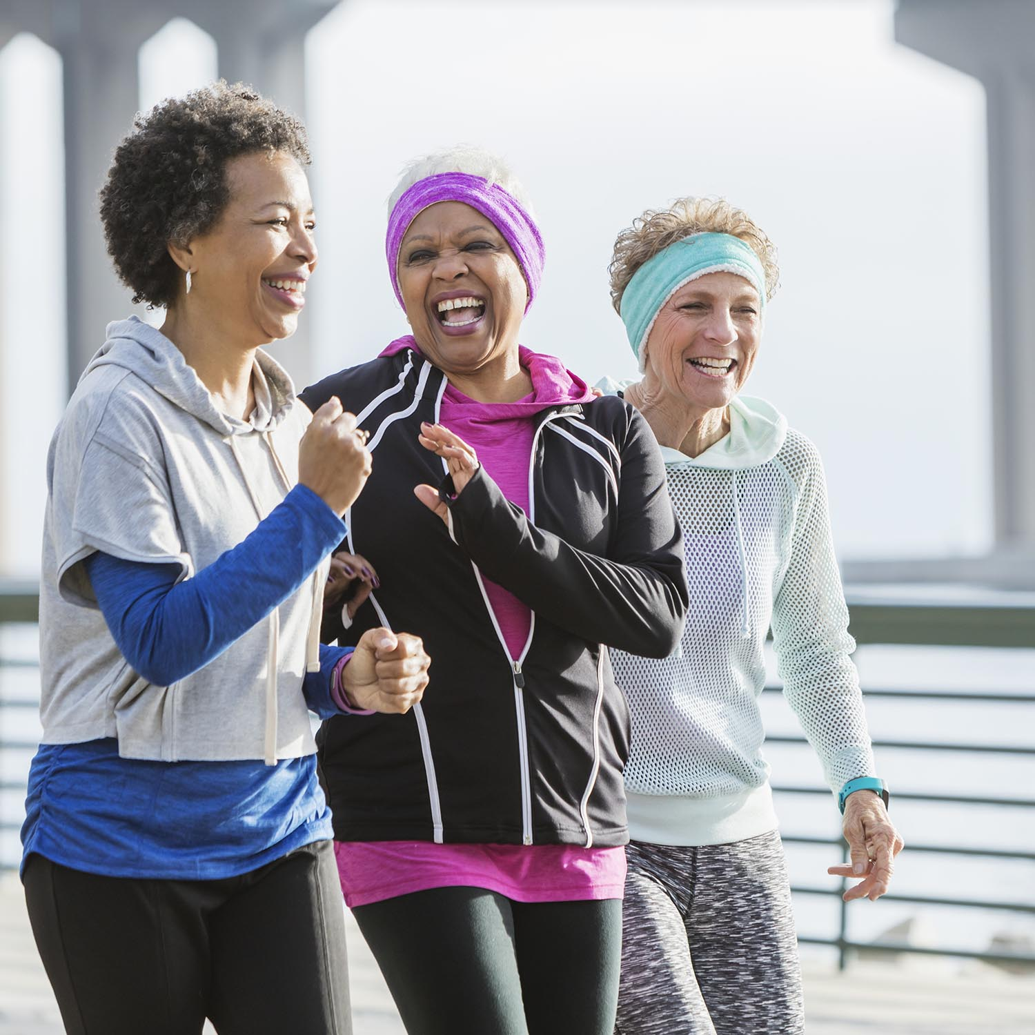 Three multi-ethnic women exercising together, power walking side by side on a city waterfront. The African-American woman with black hair is in her 50s. Her friends are senior women in their 60s.