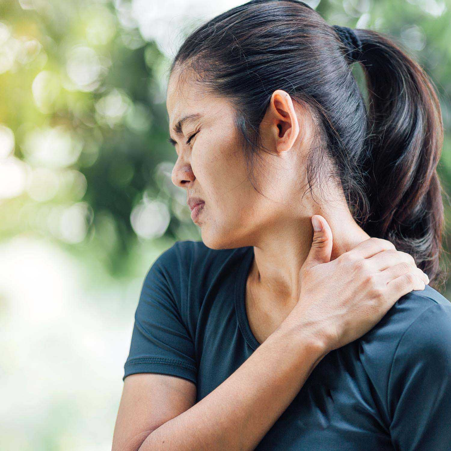Woman rubbing neck in pain