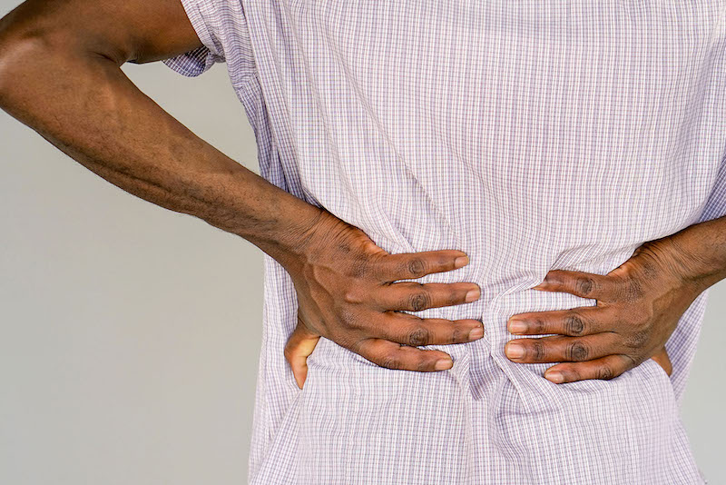 Person grasping lower back in pain