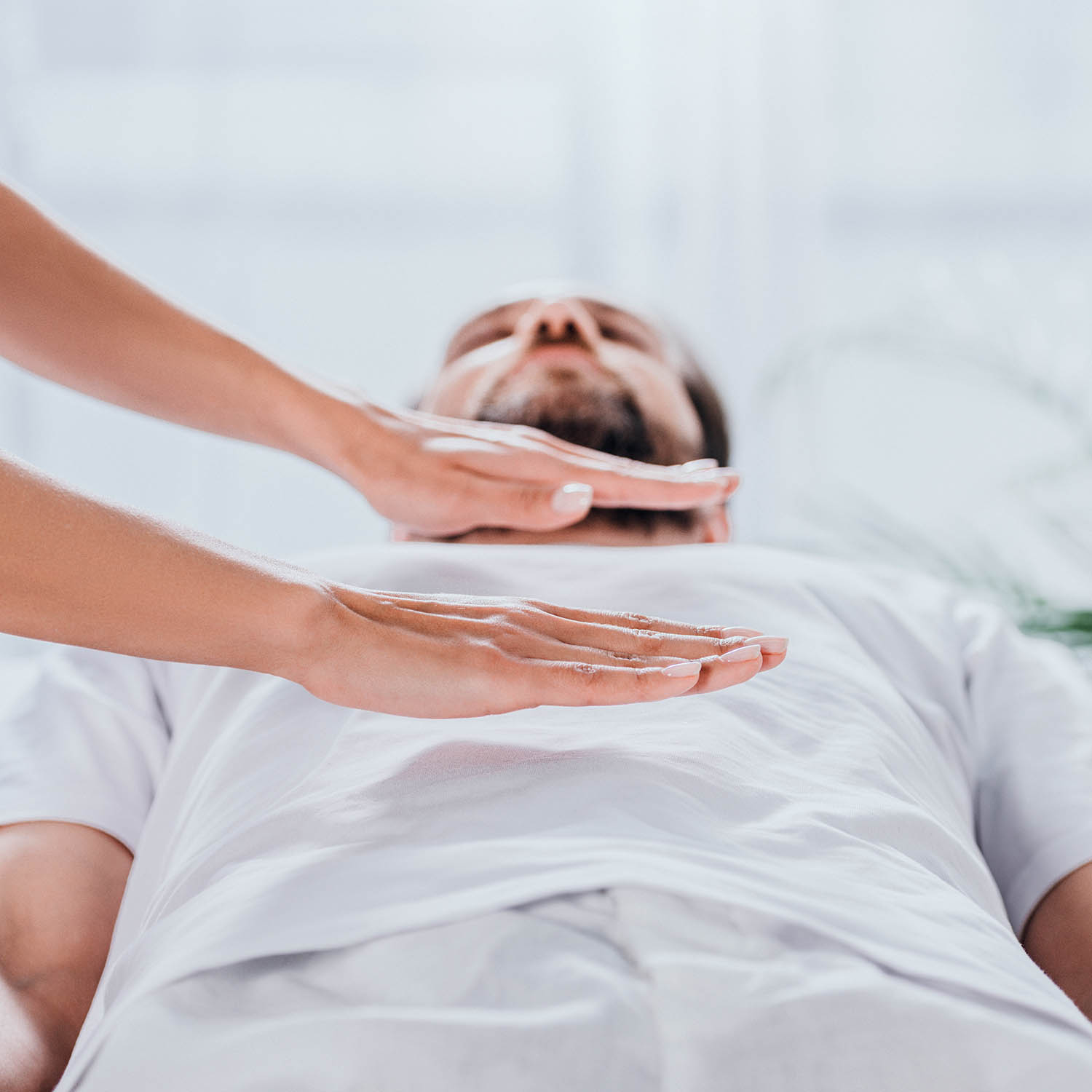 A man with a Reiki practitioner's hands hovering above him.