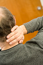 Man holding neck in pain.