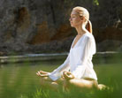 Woman meditating by stream