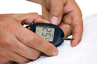 Diabetic person checks blood sugar level.
