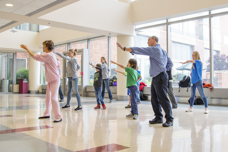Tai chi instructor leading a class of adults and children.