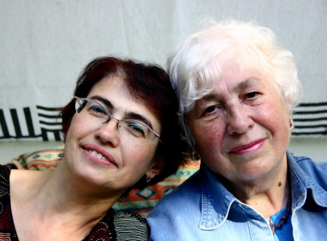 A middle-aged woman and a senior woman sitting on a couch