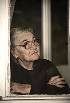 An elderly woman looks out the window