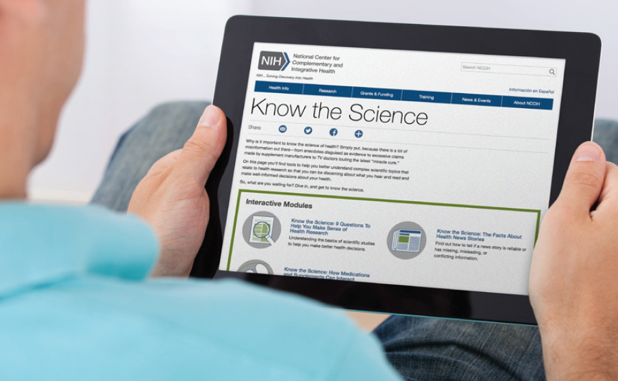 Photo of a person holding a computer tablet showing the NCCIH Know the Science web page.