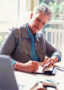 Woman signing a check.