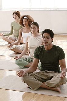 People in a meditative pose during a class on mats.