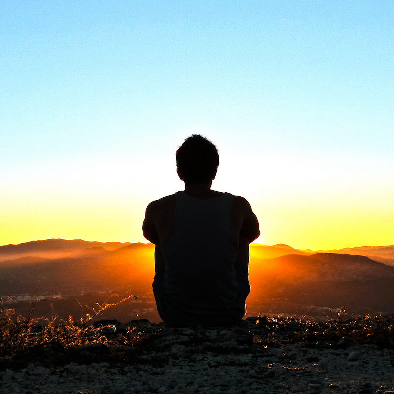 Man meditating during sunrise