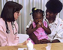 Uma enfermeira fala para uma mãe americana Africano, que tem sua filhinha no colo.
