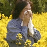 Woman sneezing in a field of flowers. © Thinkstock