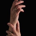 Woman holding wrist/hand.
