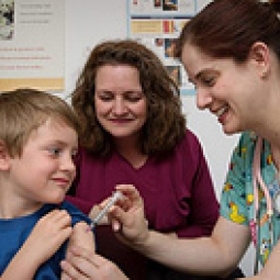 A boy with an adult recieves a shot from a health professional.