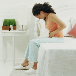 woman in pain sitting on bed with hands on her stomach