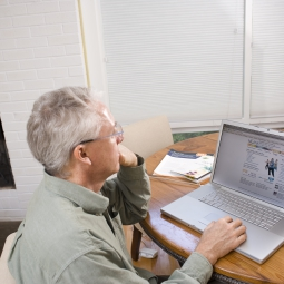 A man reviews a web site on the his laptop computer.