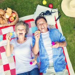 senior couple laying on picnic blanket