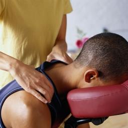 Massage therapist giving man a seated massage