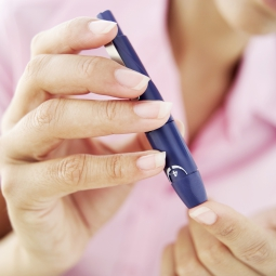 woman pricking her finger to test her blood glucose
