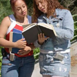 Two teen girls reviewing a book.