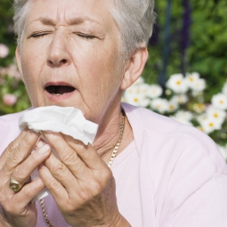 A woman outside prepares to sneeze.