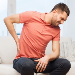 seated man in pain holding back