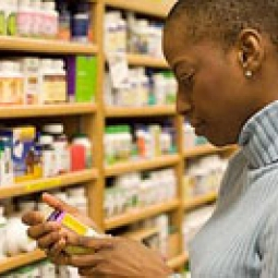 Woman looking at a pill bottle.