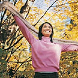 Breast cancer survivor in pink sweater outdoors