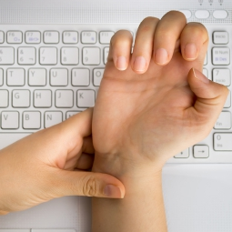 Left hand holds right hand's wrist, indicating pain.
