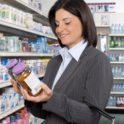 Woman comparing two dietary supplement bottle in a store