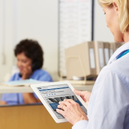 Photo of a health care provider holding an computer tablet showing the NCCIH Health Care Provider web page.