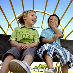 Two boys laughing while sitting on playground equipment