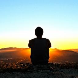 Man meditating during sunrise
