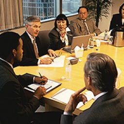 Professionals sit talking in a meeting.