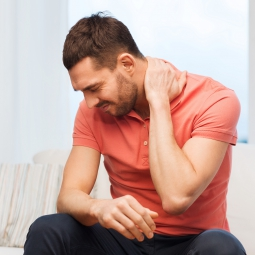 A man holds his neck in pain.