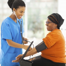 nurse taking woman's blood pressure