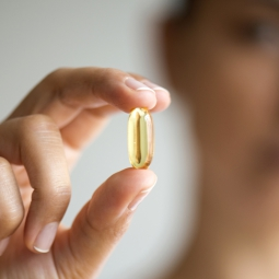 Woman holding one liquid capsule