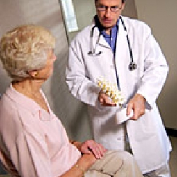 Doctor showing bone model to elderly woman