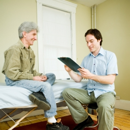 Patient sits on bed while health care professional reviews chart.