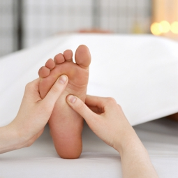 reflexologist massaging a woman's foot
