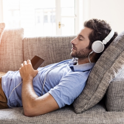 Man with headphones on lying on a couch with his eyes closed