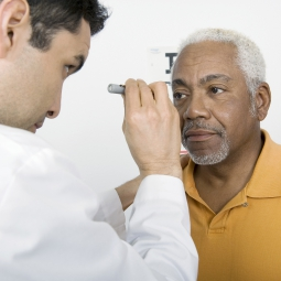 man having eyes checked by opthamologist