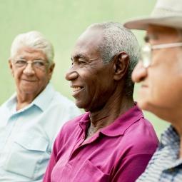 Three older men sit in discussion