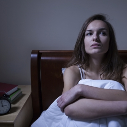 Woman under a blanket sitting up in bed