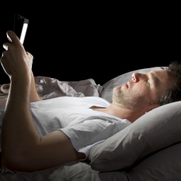 man in bed holding an electronic tablet