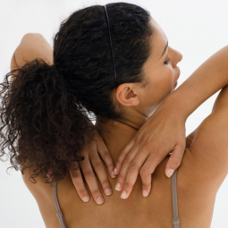 A woman reaches behind her over her sholders to touch her back.