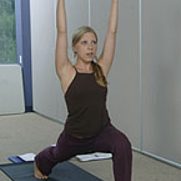 Yoga instructor demonstrates a warrior pose.